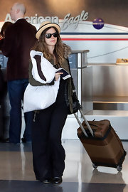 Rachel Bilson was spotted at LAX pulling a brown rollerboard.