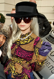 Lady Gaga teamed purple leather gloves with a colorful blouse for a day out in London.