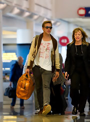 Ryan Gosling wore a thin comfy graphic tee as he got ready to jet off from LAX with girlfriend, Eva Mendes.
