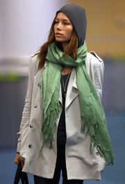 Jessica Biel accessorized with a green scarf for a splash of color to her white coat.