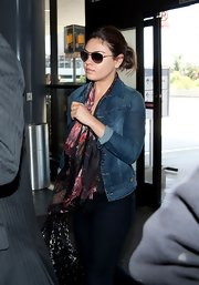 Mila Kunis' floral scarf added a feminine touch to her jean jacket during a flight out of LAX.