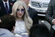 Lady Gaga looked flamboyant, as always, with her rimless, angular sunglasses and layered pearls while mingling with fans in London.