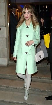 Suki Waterhouse accessorized her coat with a matching flower-embellished white purse for total cuteness.