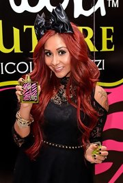 Nicole Polizzi came elaborately styled with glittery nail art, loads of bling, and a giant bow headband to the promo event for her perfume.
