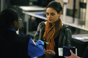 Mila Kunis paired a printed scarf with a leather jacket for her cozy airport look.