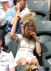 Jennifer Aniston kept the sun out with a straw hat while watching the French Open.