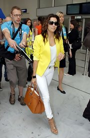Eva Longoria landed at Nice looking very stylish in a yellow blazer and white skinny jeans.