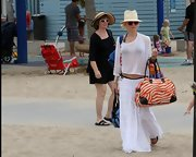 Gwen Stefani added a touch of print and color to her all-white outfit with an orange zebra bowler bag while enjoying a day at the beach.