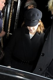 Emma Watson went for a military-inspired look with a black Eugenia Kim Elyse cap teamed with a wool coat during a night out at Mahiki Club.