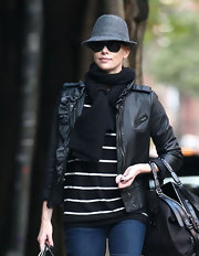Charlize wears a ruffled leather jacket over a striped blouse and with a warm black scarf.