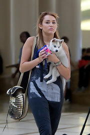 Miley Cyrus caught a flight out of LAX carrying a printed satchel and a cute husky puppy.