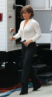Jennifer Aniston looked sleek and chic in a long-sleeve white V-neck blouse and black wide-leg pants on the set of 'Squirrels to the Nuts.'