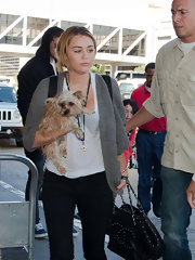Miley Cyrus was spotted at LAX carrying an edgy-glam studded tote by Chanel.