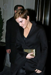 Emma Watson avoided looking too somber in her black coat and dress combo by accessorizing with a metallic gold box clutch.