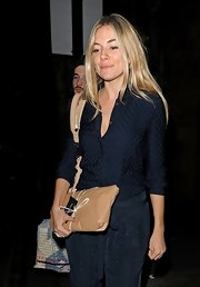 Sienna Miller was seen outside the Covent Garden Hotel wearing a pajama-chic navy silk button-down.