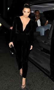 Kim Kardashian enjoyed a night out in London wearing a deep-V black velvet jumpsuit by Maria Lucia Hohan.
