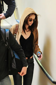 Kristen Stewart kept a low profile in a tan hoodie while catching a flight.