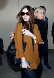 Lily Collins hid her eyes behind a pair of oversized sunnies as she made her way through LAX.