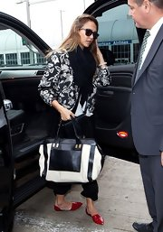 Jessica Alba arrived at LAX carrying an oversized black-and-white leather tote by Chloe.