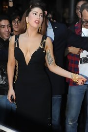 Lady Gaga teamed layers of gold bracelets with the iconic Versace safety-pin dress for a night out in Milan.