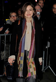 Keira Knightley wore a colorful knit scarf for a fun pop to her black coat.