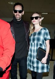 Kate Bosworth teamed a dark blue zip-around clutch with a plaid shift dress for her airport look.