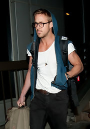 Ryan Gosling looked determined to get past the airport paparazzi while wearing a unique denim hooded vest.