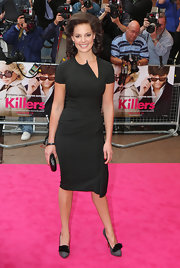Katherine dons a slim fitting little black dress with a zip opening at the neckline.