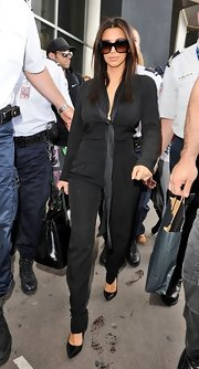 Kim Kardashian looked trendy in a black tie-neck jumpsuit as she touched down in Nice.