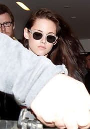 Kristen Stewart accessorized with a pair of white-framed shades for a flight.