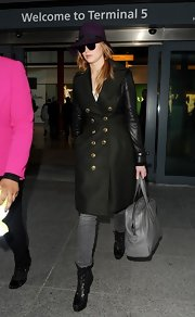 Jennifer Lawrence arrived at Heathrow wearing edgy-chic black lace-up boots with a leather-sleeve coat.