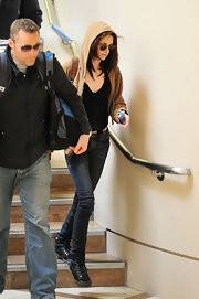 Kristen Stewart paired skinny jeans with a tan hoodie and a black V-neck tee for a flight.