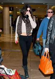 Kylie Jenner styled her sweater with a leopard-print scarf.