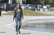 Mila Kunis was spotted out on a stroll wearing skinny jeans, a cardigan, and a leather jacket.