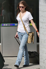 Anna Kendrick completed her travel look with a pair of ripped jeans.