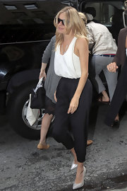 Sienna Miller completed her breezy outfit with a pair of textured black harem pants.