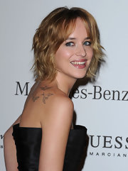 Wearing a strapless dress, Dakota Johnson proudly showed off her bird tattoo.