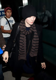 Rooney Mara teamed a striped scarf with a coat and a beanie for total warmth during her flight.