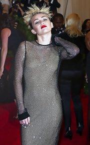 Miley Cyrus nailed the punk theme with this statement ring (by Eddie Borgo), fishnet dress, and spiked hair combo at the 2013 Met Gala.