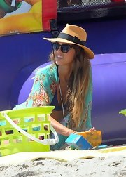 Jessica Alba kept the rays out with a cute bow-adorned straw hat while enjoying a day at the beach.