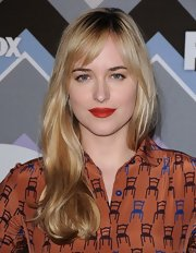 Dakota Johnson chose rich red lipstick for a jolt of color to her look.