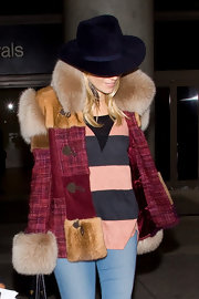 Sienna Miller tried to go incognito at LAX in a dark purple fedora.