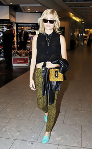 Pixie Lott showed some abs in a sheer black tie-waist blouse while making her way through Heathrow Airport.