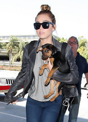 Miley Cyrus caught a flight out of LAX wearing classic black wayfarers by Dolce & Gabbana.