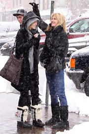 Dakota Johnson stayed warm and toasty with a pair of fur boots while shopping in Aspen.