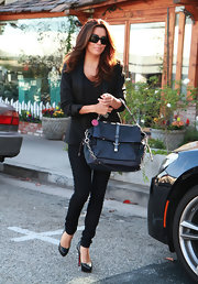 Eva Longoria finished off her all-black ensemble with a Coach leather tote.
