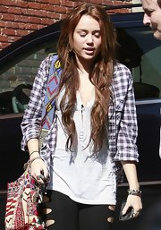 Miley Cyrus was tomboy-chic in a plaid button-down layered over a white shirt while visiting a recording studio.