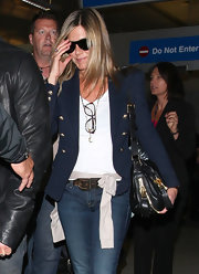 Jennifer Aniston looked sharp in a navy blazer with gold buttons as she arrived on a flight at LAX.