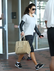 Kim Kardashian accessorized her workout getup with a stylish nude suede tote by Celine.