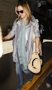 Kate Hudson caught a flight wearing a shiny slate-blue trenchcoat.